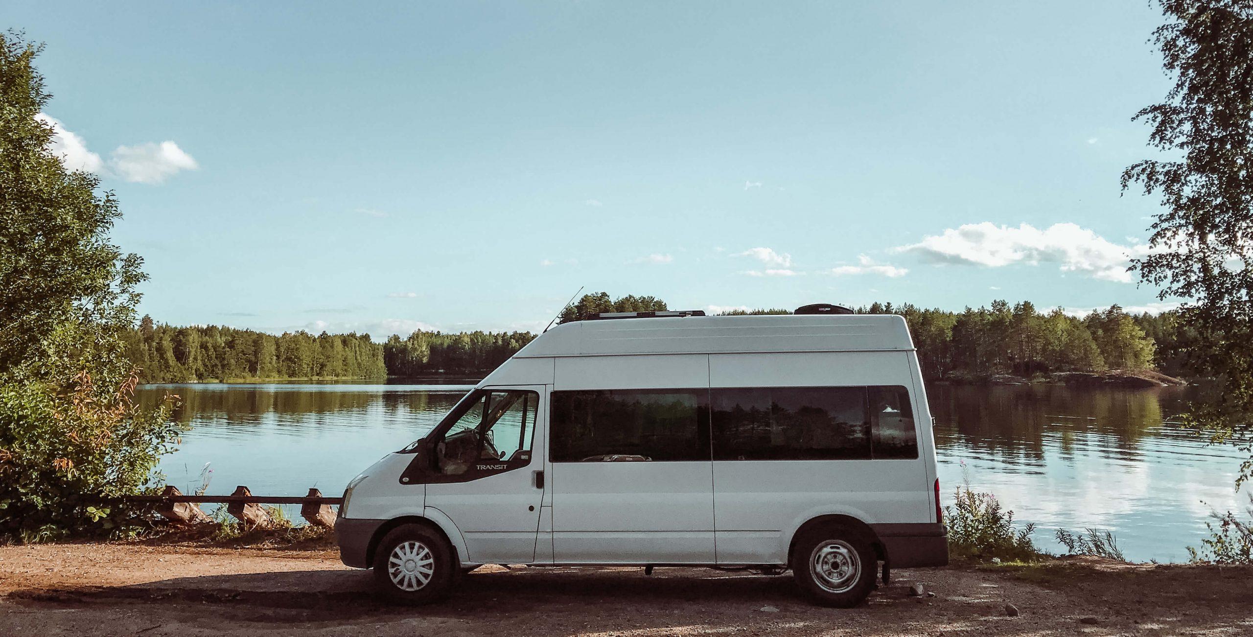 valkoinen ford transit järvimaisemassa.