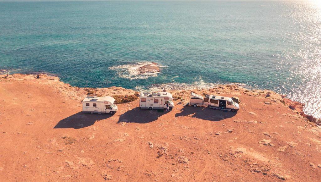 Kolme asuntoautoa parkissa auringossa kalliolla, meri taustalla.