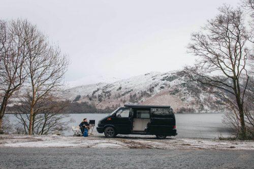 retkeilyauto ja retkeilijä luonnon äärellä talvisessa maisemassa.