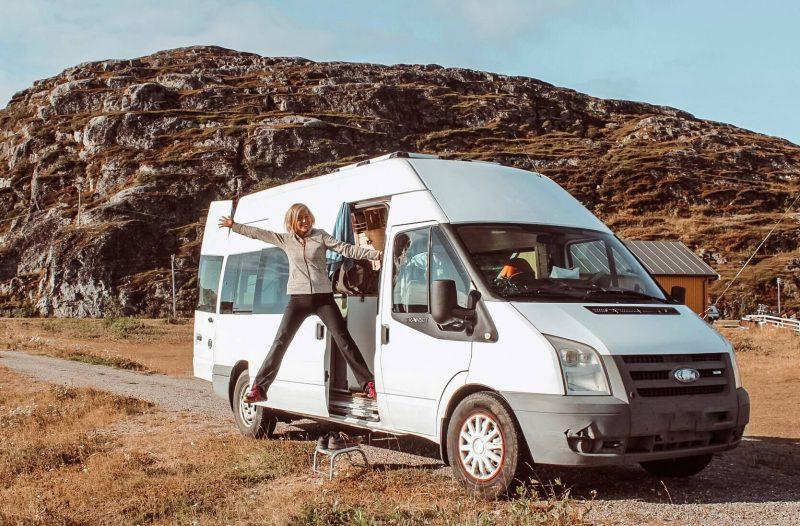 iloinen retkeilijä ja valkoinen Ford Transit -campervan.