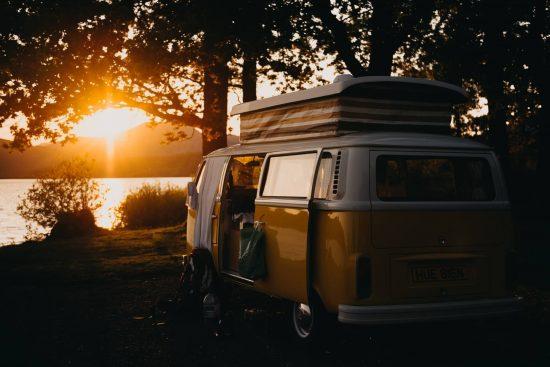 perinteinen retkeilyauto luonnon helmassa ilta-auringossa.