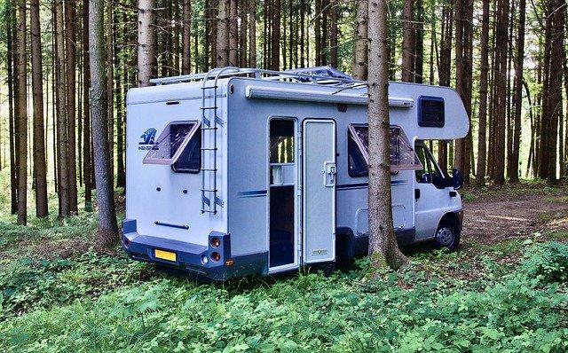 alkovimallinen asuntoauto parkissa metsässä.