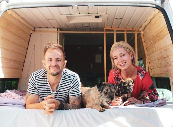 pariskunta ja kaksi borderterrieriä makaa retkeilyauto sängyllä ja hymyilee kameralle.