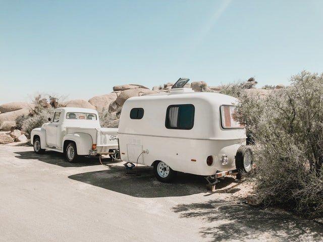 retrohenkinen valkoinen asuntovaunuyhdistelmä aurinkoisessa hiekkatien varressa.