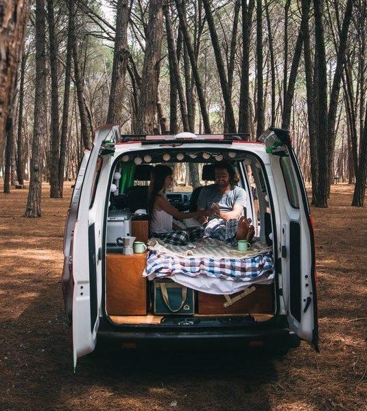 retkeilyauto takaapäin kuvattuna metsikössä takaovi auki, sängyllä istuu pariskunta.
