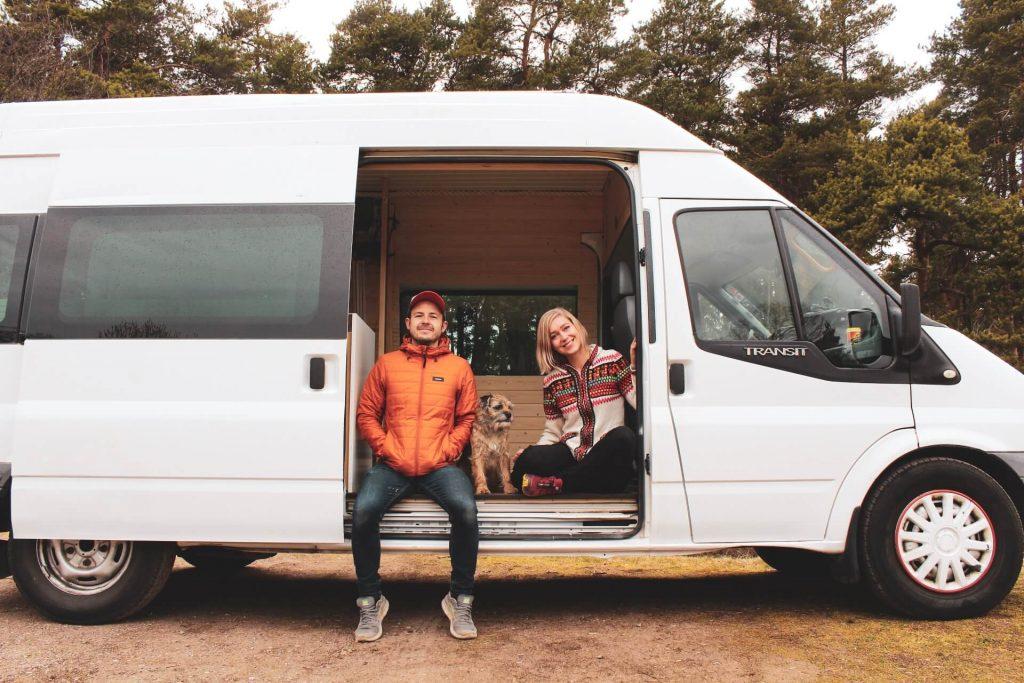 hymyilevä pariskunta ja valkoinen ford transit retkeilyauto.