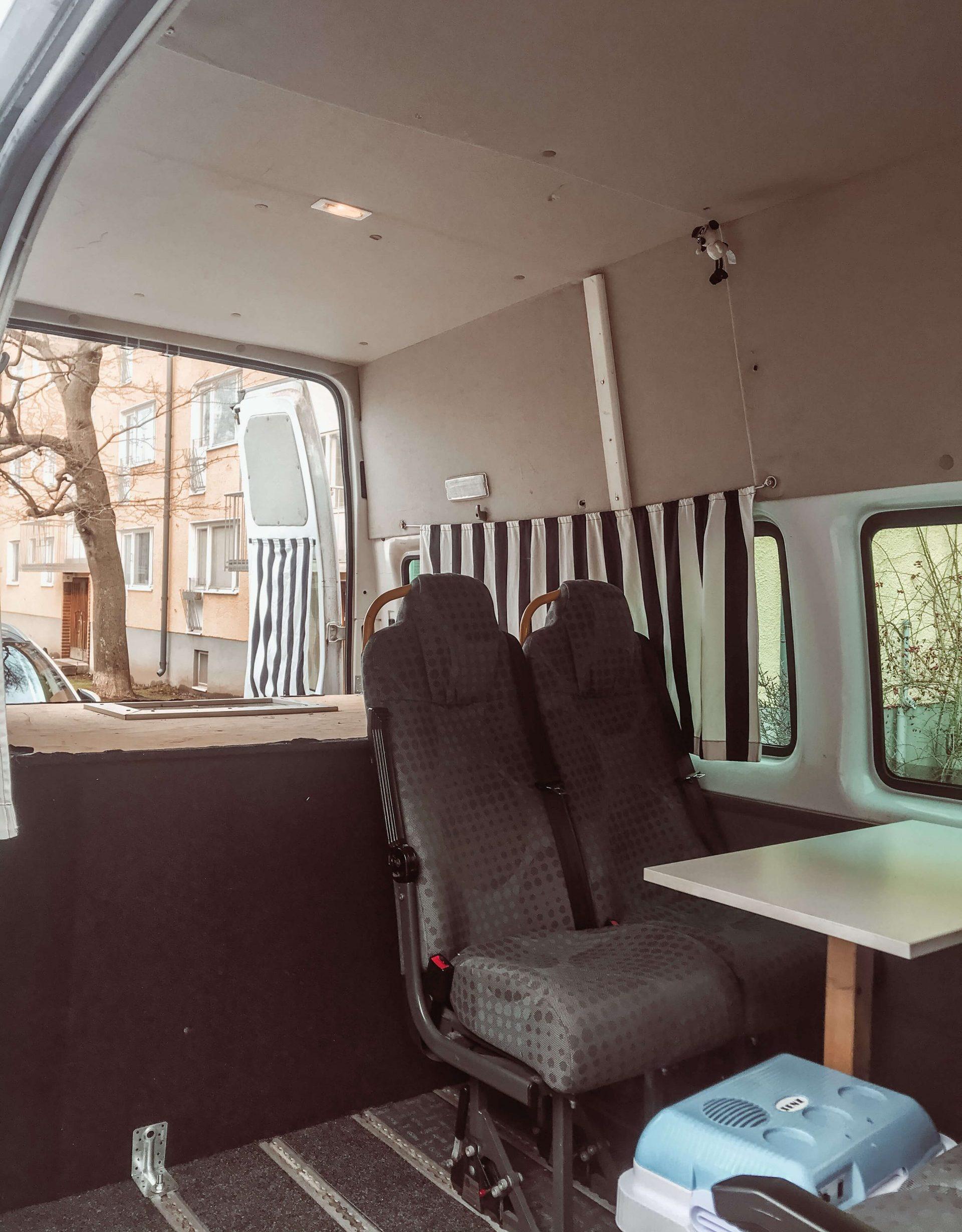 retkeilyauton sisätilat kuvattuna, kaksi penkkiä, pöytä ja yksinkertainen sänky.