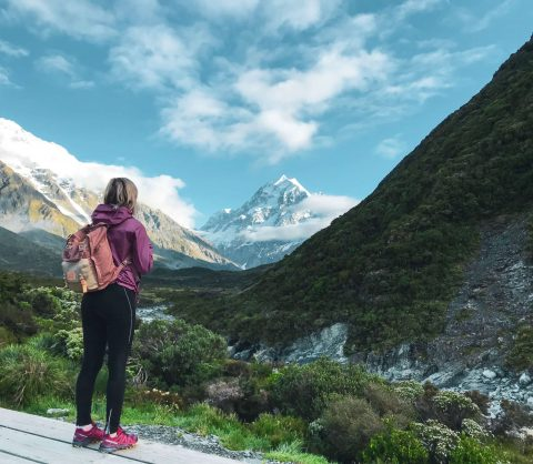 Nais-vaeltaja ja maisema Mt. Cook -vuorelle päin.