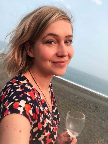 Retkeilijä Kaikouran rannalla viinilasillisen kanssa.
