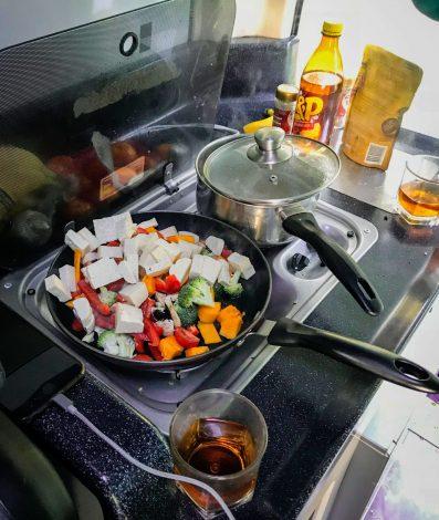 Campervanin keittiössä ruoka valmistumassa.