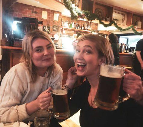 iloiset naiset ja oluttuopit ravintolan pöydän ääressä.
