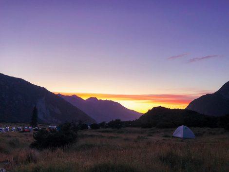 kuva auringonnoususta leirintäalueella, teltta ja vuoret.