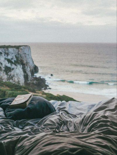 näkymä retkeilyauton sängystä merelle ja kallioille.
