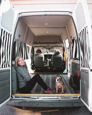 nuori nainen ja borderterrieri istuvan tyhjässä pakettiautossa.