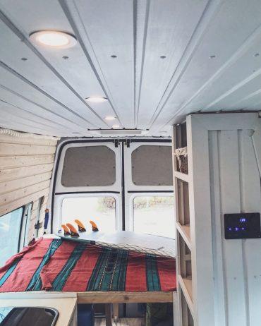 camperavnin sisätilat, surffilauta sängyn päällä.