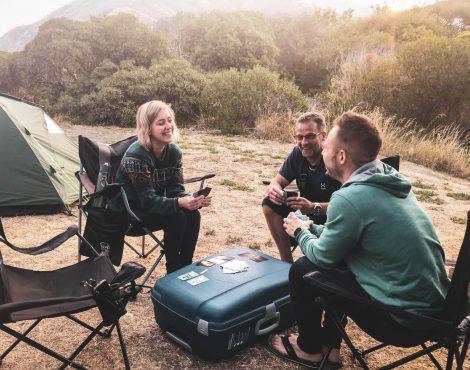 retkeilijät pelaamassa korttia leirintäalueella.