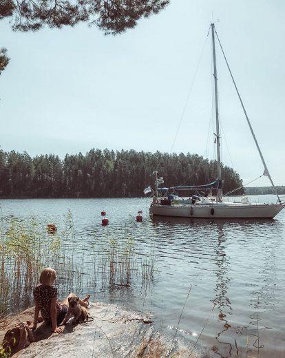 Punkaharjun järvimaisemaa, rantakallio sekä purjevene.