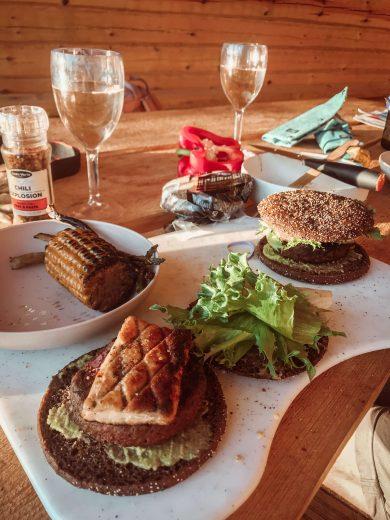 viinilasilliset ja itsetehdyt ruisburgerit laavun pöydällä.
