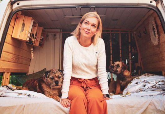 bloggaaja sekä kaksi borderterrieriä campervanin sängyllä.