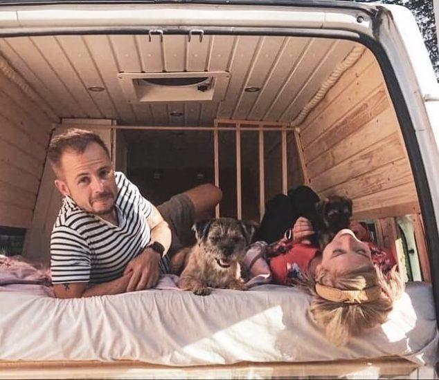 kaksi borderterrieriä ja pariskunta campervanin sängyllä.