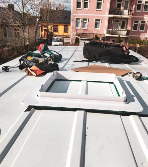 Ford Transit -pakettiauton katolla työkalut ja asennettava kattotuuletin.