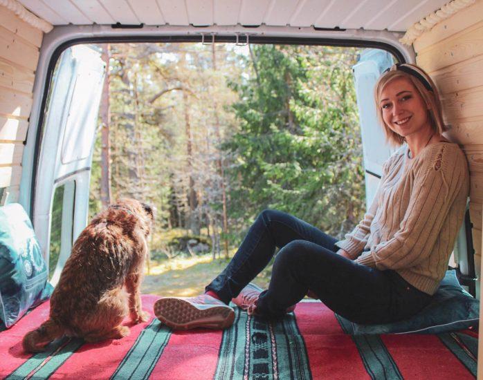 bloggaaja ja borderterrieri istuvat campervanin sängyn vanerin päällä.