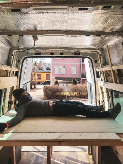 campervanin tuunaaja makaa sänkyvanerin päällä pakettiautossa.