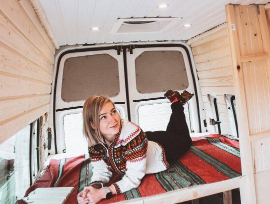 Bloggaaja itsetehdyn campervanin vanerisängyn päällä.