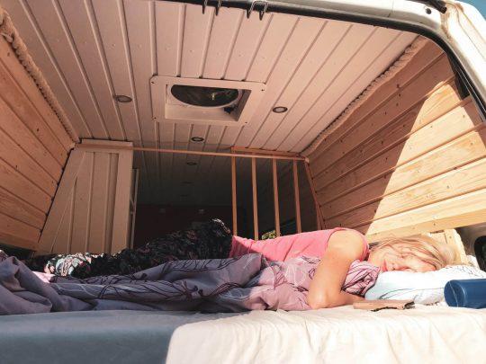 Retkeilijä lepäämässä campervanin sängyssä aamuauringossa.