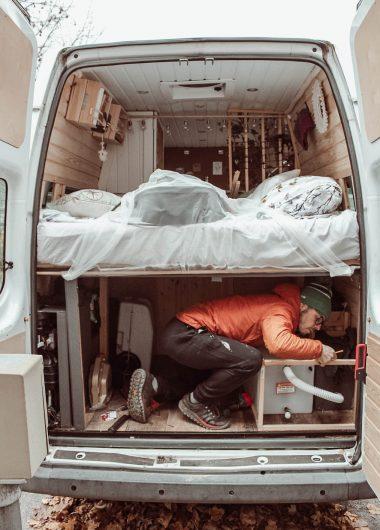 Mies fiksaa retkeilyauton sängyn alaosaa.
