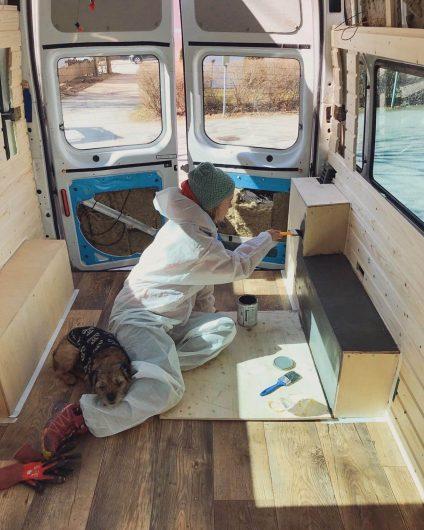 pakettiauton tuunaaja maalaustöissä auton sisällä borderterrierin kanssa.