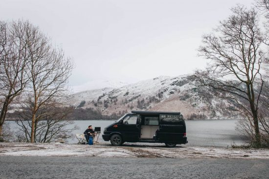 Retkeilyauto lumisessa maisemassa.