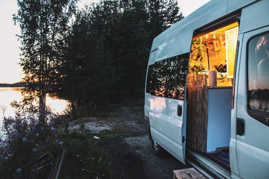 Retkeilyauton Saimaan rannalla iltavalaistuksessa.