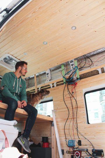 sähkötyöläinen ja borderterrieri sähkötöiden äärellä campervanin sisätiloissa.