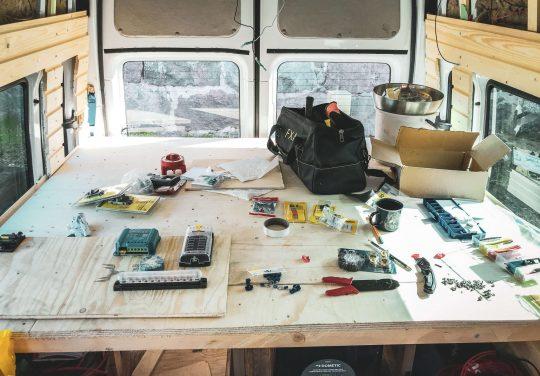 Sähkölomponentteja pakettuauton sängyn vanerin päälle levitettynä