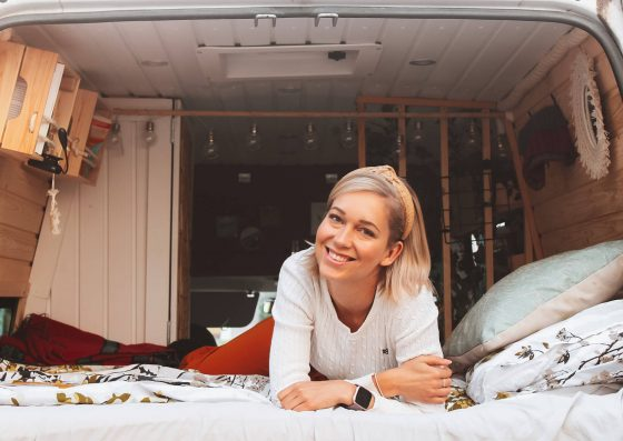bloggaaja hymyilee retkeilyauton sängyllä kameralle.