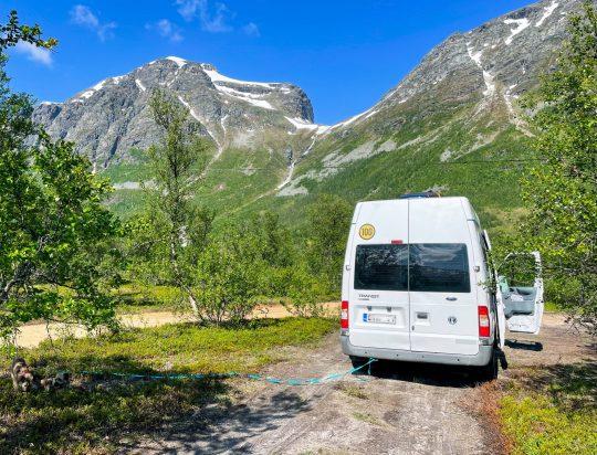 Retkeilyauto parkissa metsätiellä, vuoret taustalla.