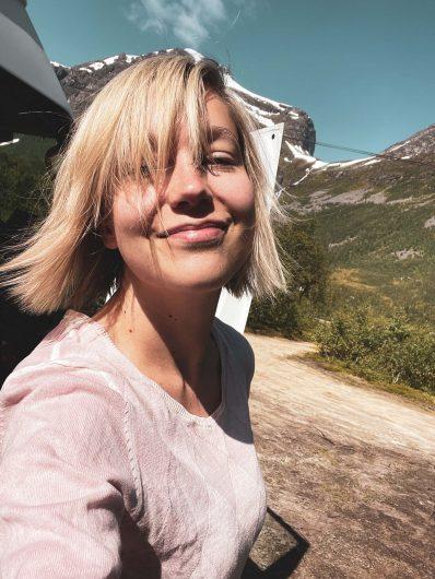 Hymyilevä retkeilijä auringonpaisteessa.