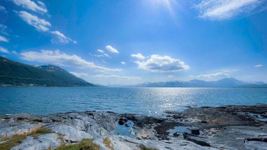 Auringossa kimmeltävä vuono ja rantakalliot.