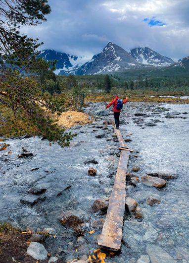 Retkeilijä tasapainoittelee lankuilla joenylityksessä Pohjois-Norjassa.