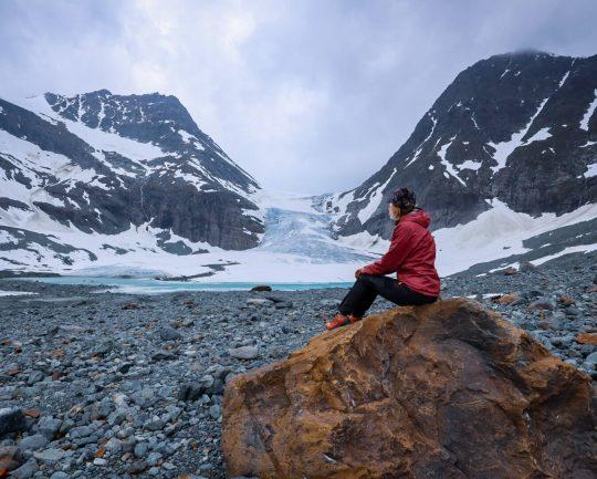 Retkeilijä istumassa kivellä Steindalsbreen-jäätikön edustalla.