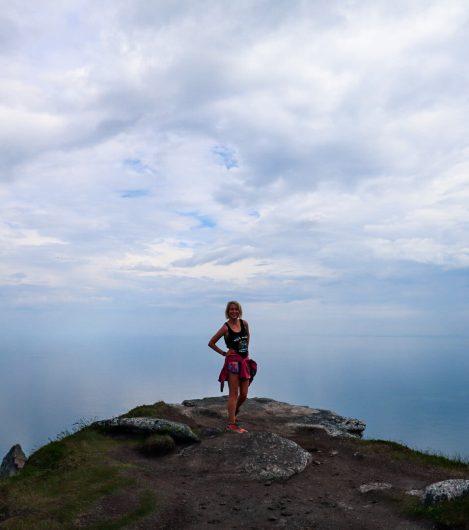 Vaeltaja seisoo Måtindenin huipulla takanaan merimaisema.