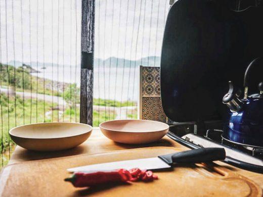 Retkeilyauton keittiö, rantamaisema taustalla.