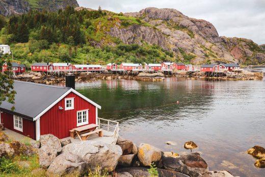 Nusfjordin kylän punaisia kalastajamökkejä vuonon rannalla.