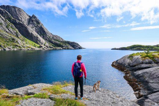 Mies ja borderterrieri Nusfjordin rantakallioilla meren äärellä.