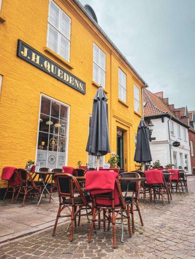 Keltainen kahvilarakennus ulkopöytineen, Ribe.