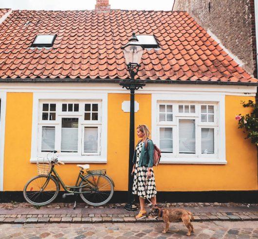Bloggaaja kävelemässä Riben kaduilla, keltainen talo taustalla.